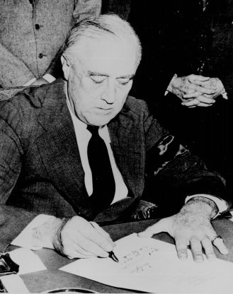 President Franklin D. Roosevelt signs the war declaration